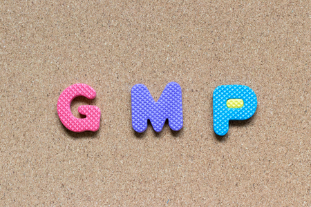 Color foam alphabet in word GMP (Abbreviation of good manufacturing practice) on cork board background Stock Photo
