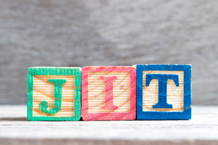 Color letter block in word JIT (abbreviation of just in time) on wood background Stockfoto