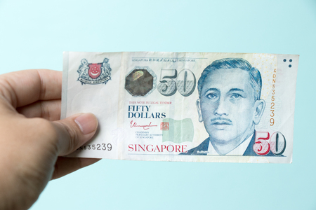 Business man hold 50 Singapore dollar bank note on blue concrete background