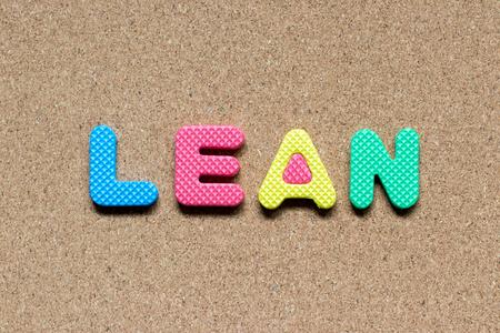 Color foam alphabet in word lean on cork board background