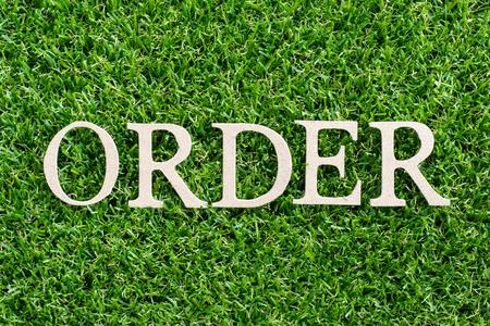 Lettera di legno in ordine di parola su sfondo verde erba artificiale Archivio Fotografico - 107603975