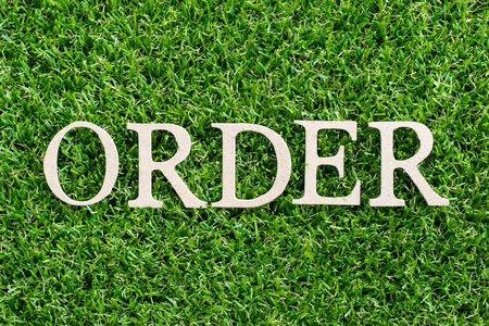 Wood letter in word order on artificial green grass background Archivio Fotografico - 107603975
