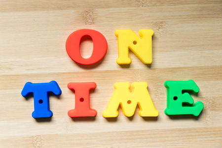 Color plastic alphabet in word on time on wood background