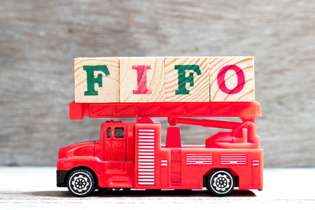Toy fire ladder truck hold letter block in word FIFO (Abbreviation of first in first out) on wood background