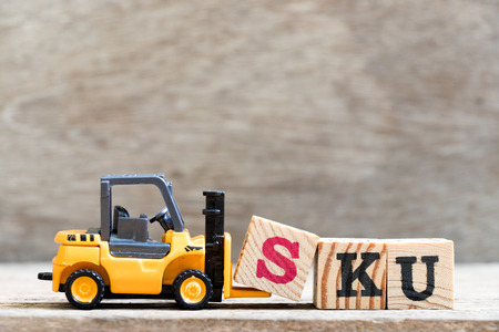Toy forklift hold letter block S in word SKU (abbreviation of stock keeping unit) on wood background Stock fotó