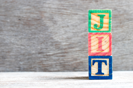 Color letter block in word JIT (abbreviation of just in time) on wood background Stock Photo