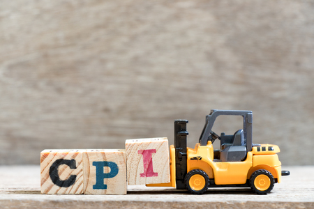 Toy forklift hold letter block I in word CPI on wood background