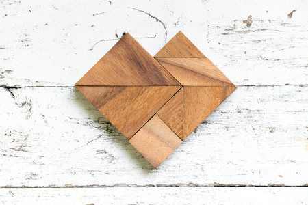 Tangram puzzle in heart shape on old white wood background