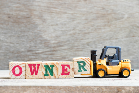 Toy forklift hold letter block r to complete word owner on wood background
