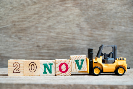 Toy forklift hold block V to complete word 20nov on wood background (Concept for calendar date 20 in month November)