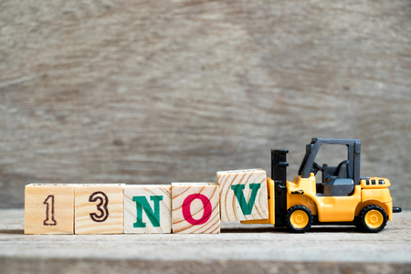 Toy forklift hold block V to complete word 13nov on wood background (Concept for calendar date 13 in month November) Stock Photo