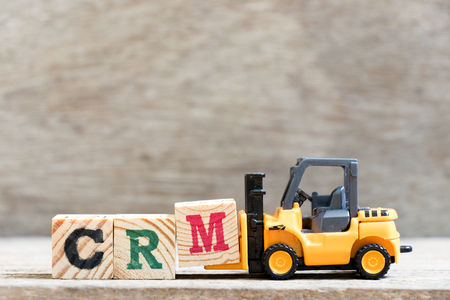 Toy forklift hold letter block M in word CRM (Abbreviation of Customer Relationship Management) on wood background