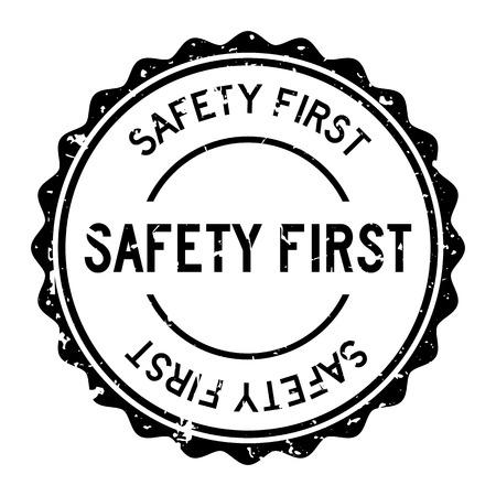 Grunge black safety first word round rubber seal stamp on white background Illustration