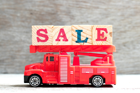 Toy fire ladder truck hold letter block in word sale on wood background Stock Photo
