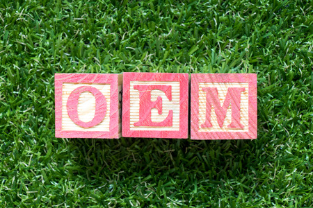 Color wood block in word OEM (Abbbreviation of Original Equipment Manufacturer) on artificial green grass background Фото со стока