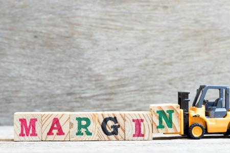 Toy forklift hold letter block N to complete word margin on wood background Reklamní fotografie