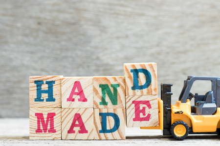 Toy forklift hold letter block D,E to complete word handmade on wood background
