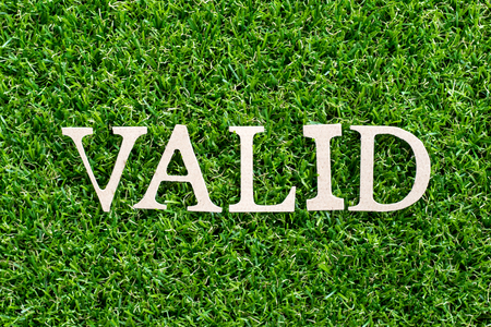 Wood letter in word valid on artificial green grass background