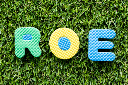 Color alphabet letter in word ROE (Abbbreviation of Return on equity) on artificial green grass background 版權商用圖片