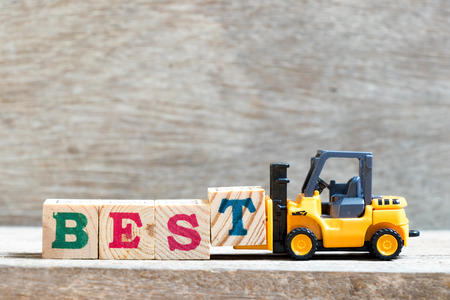 Toy forklift hold letter block t to complete word best on wood background