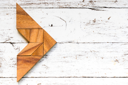 Tangram puzzle in arrow shape on old white wood background