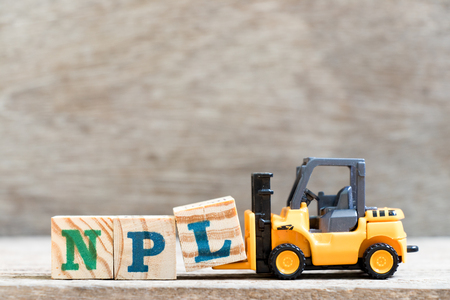 Toy forklift hold letter block L in word NPL (abbreviation of Non Performing Loan, Non-Patent Literature) on wood background