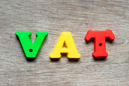 Color alphabet letter in word VAT (Abberviation of Value added tax) on wood background Archivio Fotografico