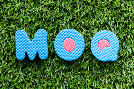 Color alphabet letter in word MOQ (Abbreviation of Minimum Order Quantity) on artificial green grass background
