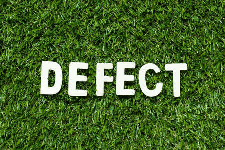 Alphabet letter in word defect on artificial green grass background Reklamní fotografie
