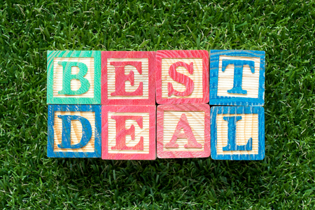 Color wood block in word best deal on artificial green grass background 免版税图像