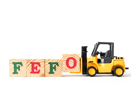 Toy forklift hold letter block o to complete word FEFO (first expired first out) on white background