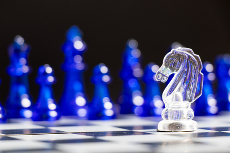 Clear knight chess piece face with blue team on black background (Concept for company strategy, business decision and encounter the problem)