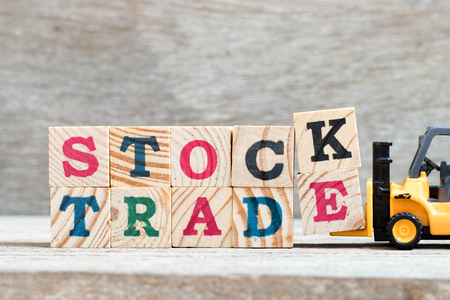 Toy forklift hold lette block k,e to complete word stock trade on wood background Stock Photo