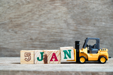 Toy forklift hold block N to complete word 5jan on wood background (Concept for calendar date in 5 month January)