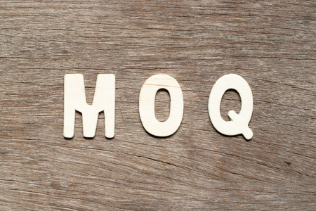 Alphabet letter in word MOQ (Abbreviation of Minimum Order Quantity) on wood background