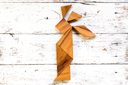 Tangram puzzle in  native american indian shape on old white wood background