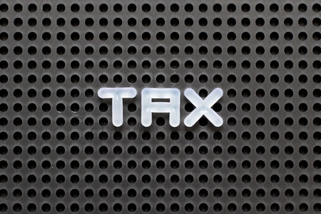 Black color pegboard with white letter in word tax