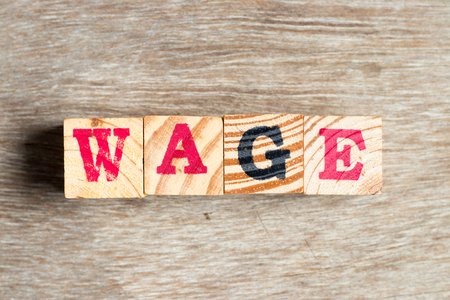 Letter block in word wage on wood background