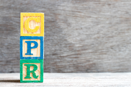 Color letter block in word CPR (abbreviation of Cardiopulmonary resuscitation) on wood background