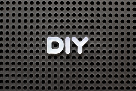 Black color pegboard with white letter in word  DIY (abbreviation of do it yourself) Stock Photo