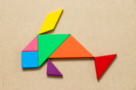 Color tangram puzzle in swimming fish shape on wood background 版權商用圖片