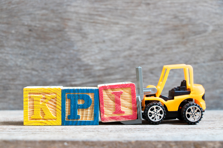 Toy forklift hold color letter block I to complete word   KPI (Abbreviation of Key performance indicator) on wood background