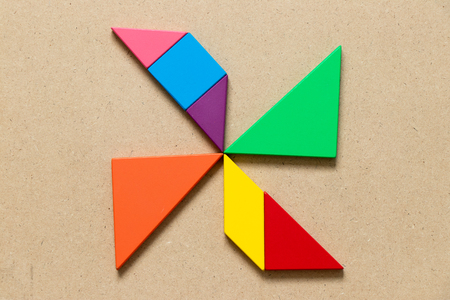 Color tangram puzzle in wind turbine shape on wood background