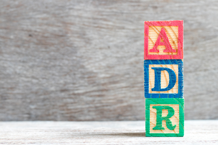Color letter block in word ADR (Abbreviation of adverse drug reaction) on wood background