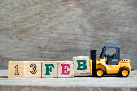 Toy forklift hold block B to complete word 13feb on wood background (Concept for calendar date 13 in month February)