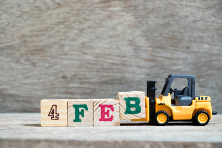 Toy forklift hold block B to complete word 4feb on wood background (Concept for calendar date 4 in month February)