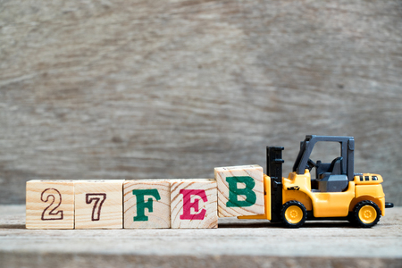 Toy forklift hold block B to complete word 27feb on wood background (Concept for calendar date 27 in month February)