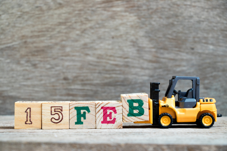 Toy forklift hold block B to complete word 15feb on wood background (Concept for calendar date 15 in month February) Stock Photo