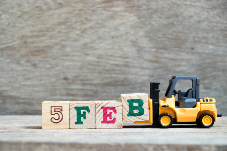 Toy forklift hold block B to complete word 5feb on wood background (Concept for calendar date 5 in month February)