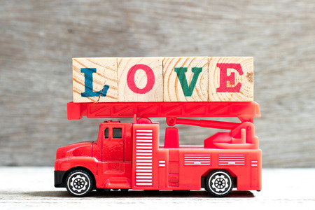 Toy fire ladder truck hold letter block in word love on wood background